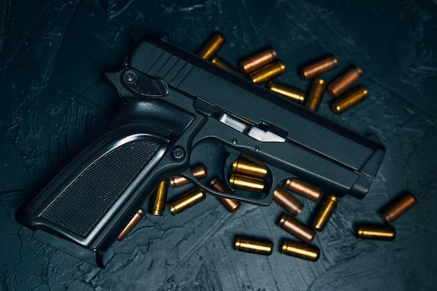 Armas de fogo automáticas com balas de pistola preta com cartuchos em armas de mesa em fundo de concreto ...