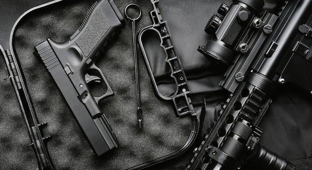 Armas e equipamentos militares para o exército, arma de espingarda de assalto (m4a1) e pistola 9mm em fundo preto.