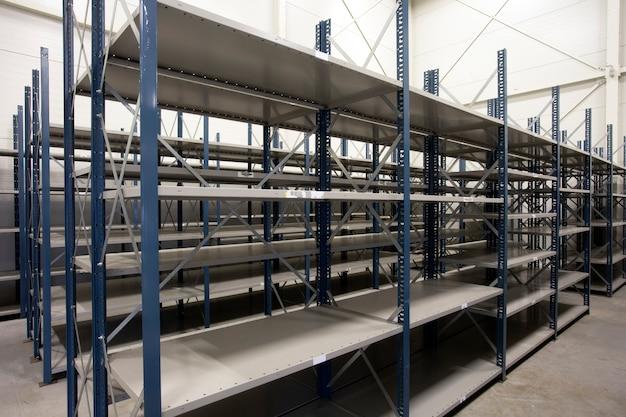Armazém enorme com prateleiras vazias dentro para design moderno de armazenamento, prateleiras de metal para distribuição