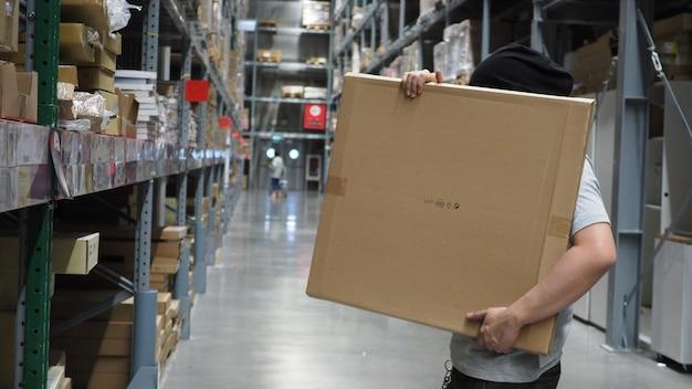 Armazém grande armazenamento ou carga para distribuição e as costas do homem estão pegando uma caixa marrom.