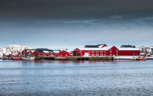 Armazém vermelho da indústria de vila de pescadores com no porto