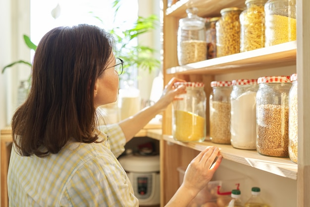 Armazenamento de alimentos, prateleira de madeira na despensa com produtos de grãos em potes de armazenamento. mulher pegando comida para cozinhar