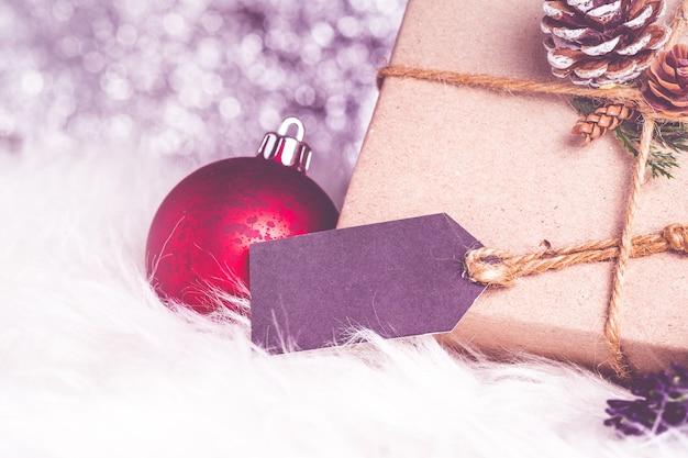 Armazenamento de papel marrom entortado na caixa presente com etiqueta de etiquetas decorada com cone de pinho e bola de natal de folha verde no fundo cintilante do bokeh
