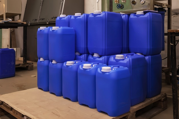 Armazenamento e armazenamento de líquidos químicos. fileiras suaves de recipientes de líquidos em paletes de madeira. plano de fundo das latas armazenadas no armazém. o conceito de armazenamento e armazenamento de mercadorias