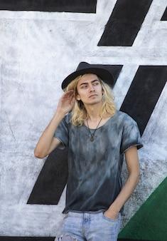Armênio atraente com um chapéu apoiado em uma parede preta e branca e olhando para o outro lado