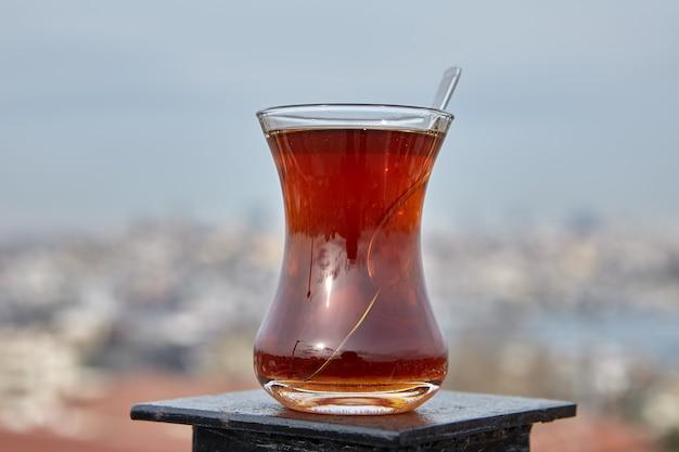 Armudu com chá turco fica em cima da cerca do telhado com vista desfocada de istambul