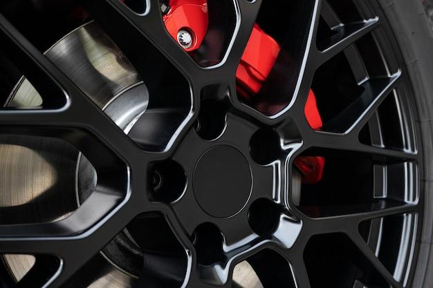 Aro da roda preta e pinça de freio vermelha de um carro esporte. fechar-se