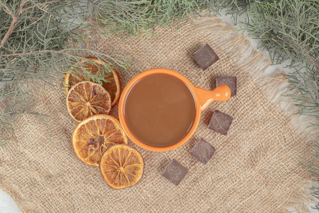 Aroma café, rodelas de laranja e chocolate sobre serapilheira.