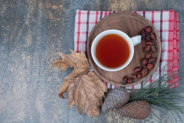 Aroma chá em xícara branca com frutos de roseira brava e pinhas na mesa de mármore