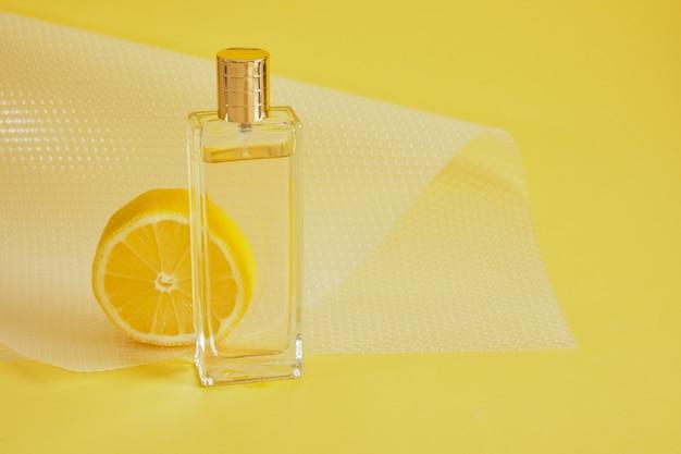Aroma cítrico, perfume com conceito de aroma de limão, fatia de limão e frasco de perfume no espaço de cópia de fundo amarelo