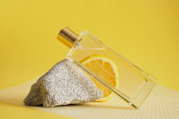 Aroma cítrico, perfume com conceito de aroma de limão, fragmento de bloco de concreto, fatia de limão e frasco de perfume em fundo amarelo