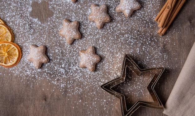 Aroma de gengibre de natal estrelas com laranja e canela em açúcar em pó em uma velha mesa de madeira marrom. bolo caseiro. vista do topo