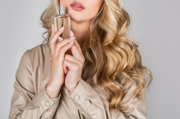 Aroma de spray de mulher de frasco de perfume. mulher segurando uma garrafa de perfumes.