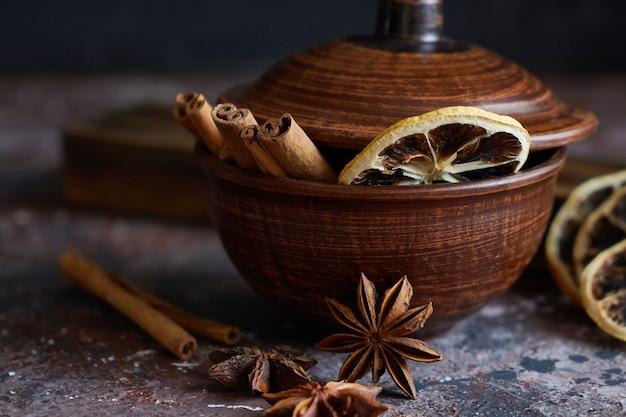 Aroma quente com vinho: canela, anis estrelado, casca de laranja em uma tigela marrom