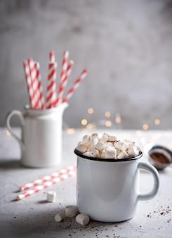 Aroma quente de chocolate com marshmallows e um tubo de papel vermelho sobre uma mesa cinza. espírito de natal. visão frontal e macro