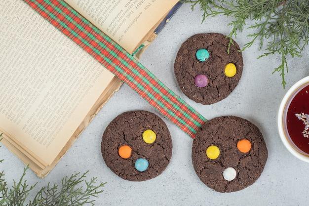 Aroma xícara branca de chá de ervas com biscoitos de chocolate na superfície cinza