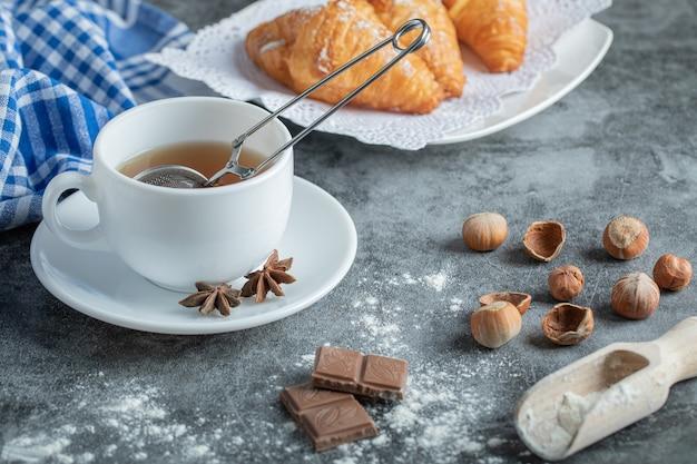 Aroma xícara de chá com deliciosos croissants.
