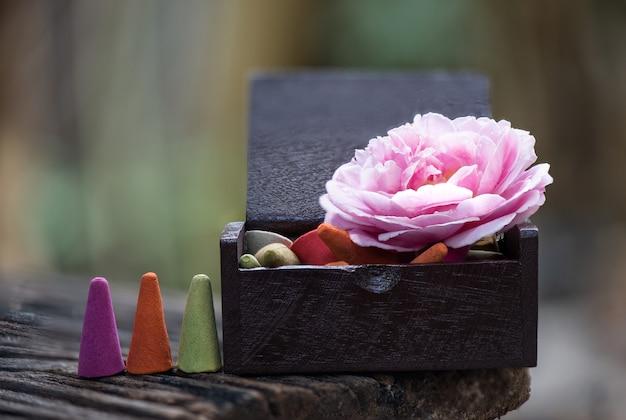 Aromaterapia com olíbano e flor de rosa damasco rosa na superfície da natureza.
