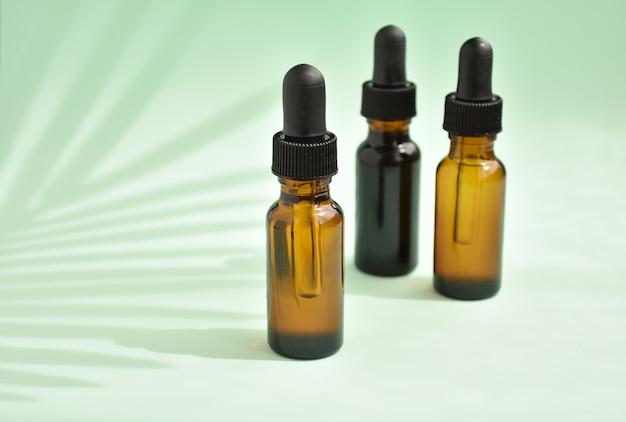 Aromaterapia, frascos conta-gotas com óleos essenciais, palma deixa sombra.