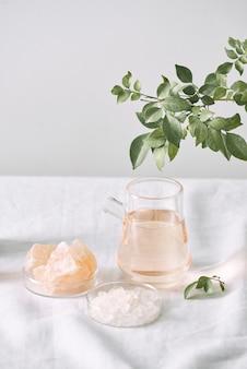 Aromaterapia. frascos pequenos de vidro com óleos cosméticos. sal de banho. folha fresca. objetos para procedimentos de spa em óleo de fundo branco, folha.