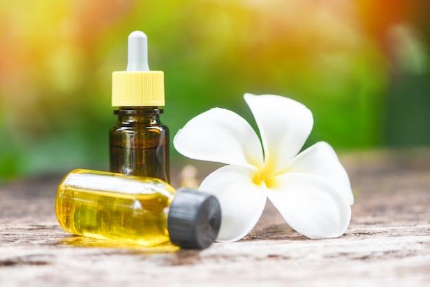 Aromaterapia garrafas de óleo de ervas aroma com flor branca frangipani plumeriaon com fundo de natureza - óleos essenciais naturais na mesa de madeira e spa minimalista orgânico