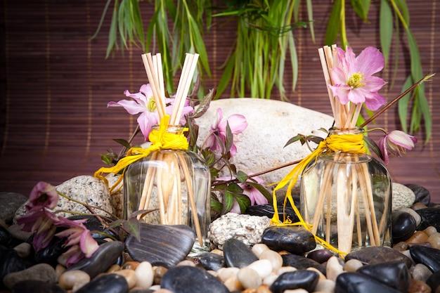 Aromaterapia, spa, tratamento de beleza e bem-estar com massagem com pedras, flores, frasco