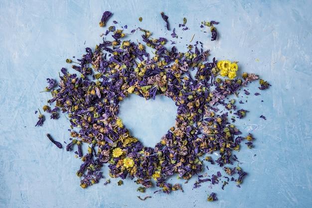 Aromático chá de ervas secas de lavanda e camomila coração solto no espaço de cópia de mesa de madeira azul