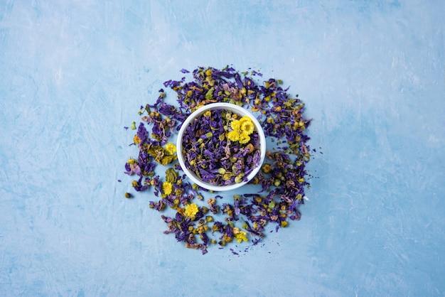 Aromático chá de ervas secas lavanda e camomila solta perto de copo branco no espaço de cópia de mesa de madeira azul