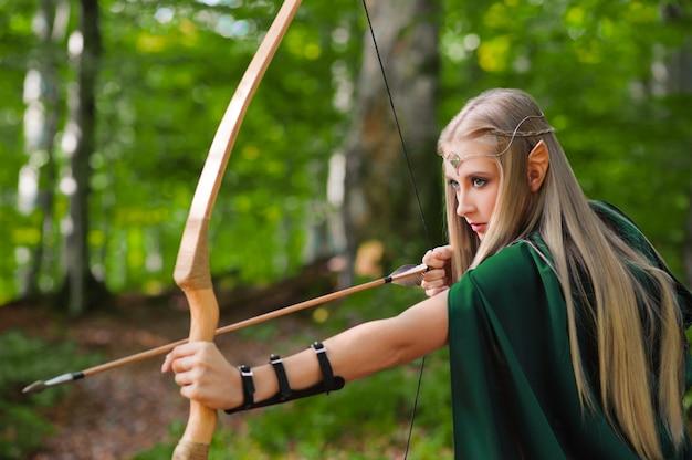 Arqueiro elfo fêmea bonito na caça da floresta com um arco