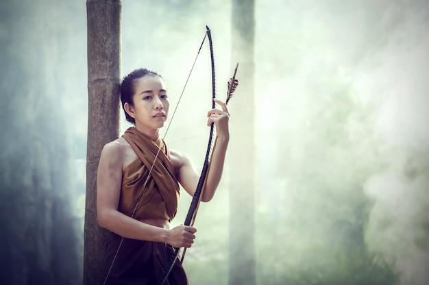 Arqueiro tailandês bonito da mulher com arco e flechas no estilo do vintage do fundo da floresta em tailândia.
