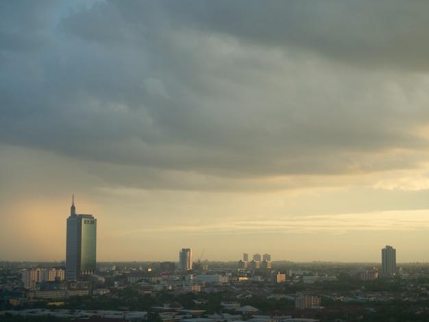 Arquitectura da cidade da cidade do unknow com nuvens grossas e luz do por do sol.