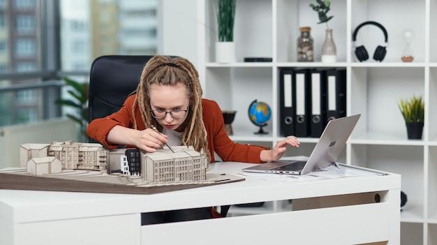 Arquiteta altamente qualificada com dreadlocks faz medições a partir de maquetes de edifícios no escritório de arquitetura