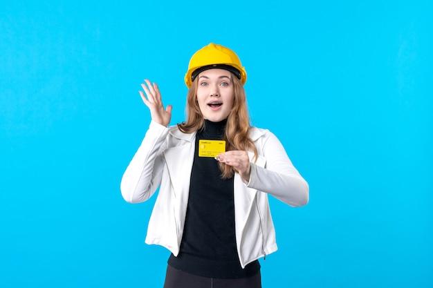 Arquiteta de frente para a mulher segurando o cartão do banco em azul