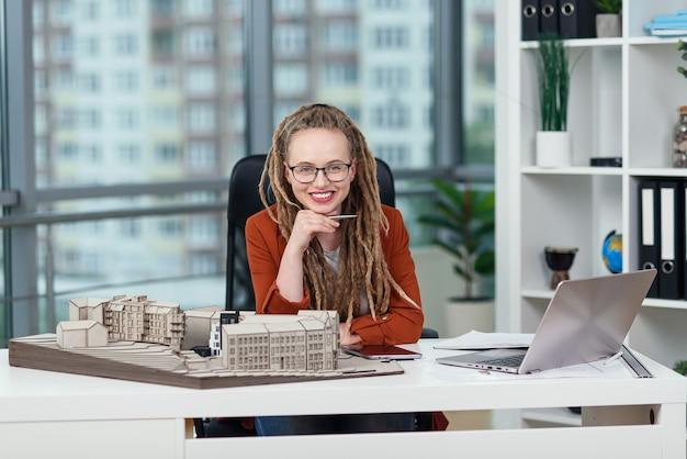 Arquiteta elegante e sorridente de óculos com dreadlocks sentada no local de trabalho com a maquete do futuro edifício