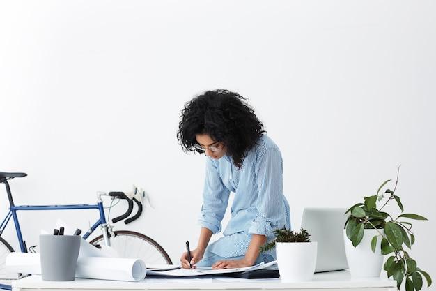 Arquiteta elegante segurando a caneta, planejando e escrevendo cálculos no caderno de desenho