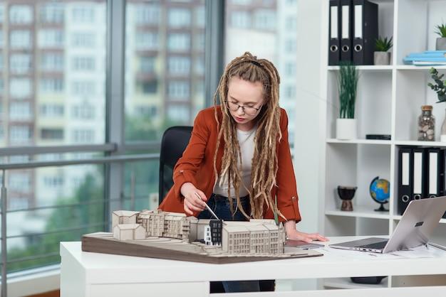 Arquiteta experiente com dreadlocks trabalhando com modelo de papelão de área residencial em