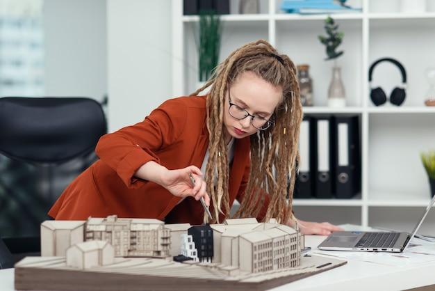 Arquiteta experiente com dreadlocks trabalhando com modelo de papelão de área residencial