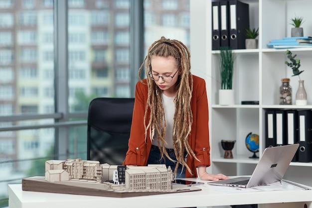 Arquiteta experiente e estilosa com dreadlocks trabalhando com um modelo de papelão da área residencial