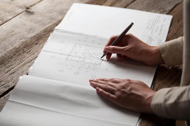 Arquiteta fazendo anotações na planta da casa