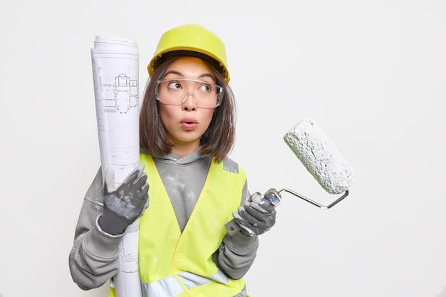 Arquiteta mulher segura rolo de pintura de planta de papel se perguntou a expressão vestida de uniforme ocupada fazendo reforma de casa isolada no branco