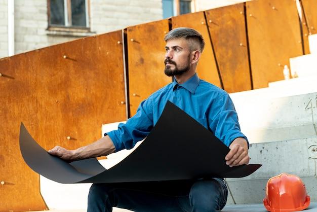 Arquiteta, sentando, e, segurando, desenhos técnicos