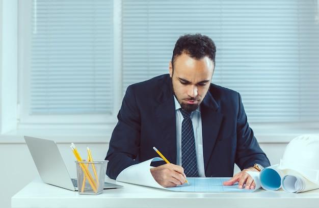 Arquiteta, sentando escrivaninha, e, trabalhando