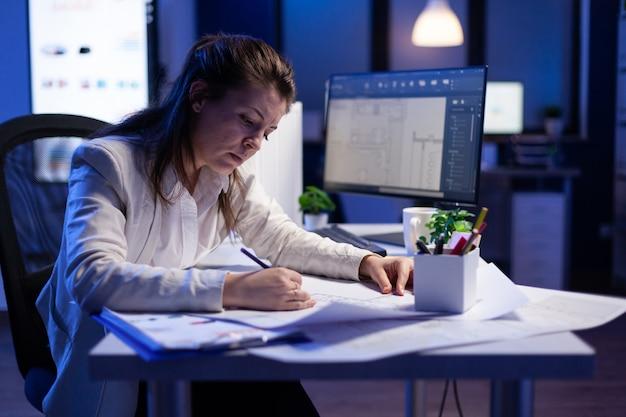 Arquiteta sobrecarregada de trabalho verificando e combinando projetos, sentada na mesa do escritório em frente ao computador
