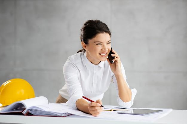 Arquiteta sorridente, tendo uma ligação com um cliente importante e anotando informações importantes.