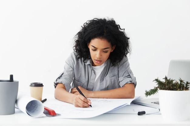 Arquiteta trabalhadora e concentrada vestindo uma camisa cinza desabotoada