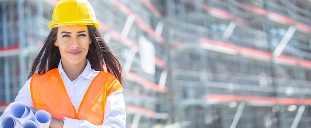 Arquiteta, vestindo colete de segurança laranja e um capacete amarelo, segura planos de construção enrolados sob a axila na frente do prédio inacabado.