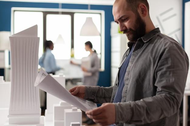 Arquiteto adulto olhando para um plano de projeto em um escritório para trabalhar em um edifício de design moderno