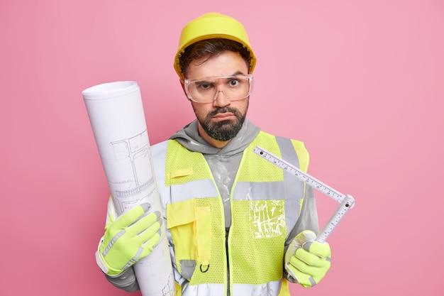 Arquiteto adulto sério, ocupado em construção, segura planta e fita métrica prepara projeto de negócios vestido com roupas de segurança