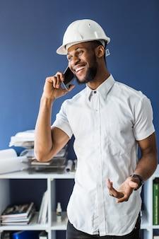 Arquiteto africano sorridente, falando no celular no escritório