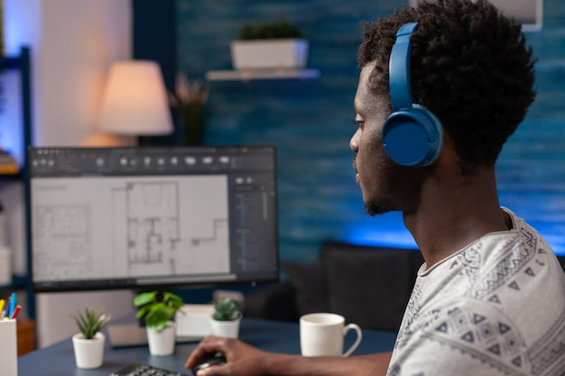 Arquiteto afro-americano com fone de ouvido sentado na mesa da sala de estar